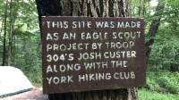 Board on a tree announcing the presence of a Scout's eagle project.