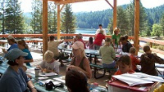 Family camping in the dining area overlooking a lake.