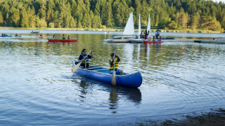 Family camping water sports - canoeing and sail boats.