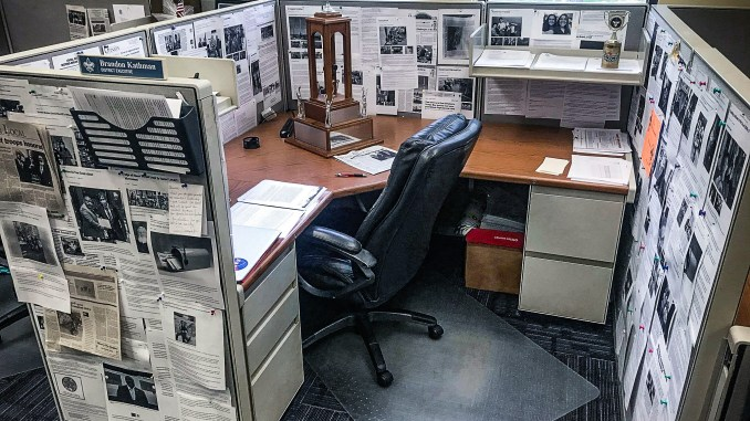 Picture of a work cubicle with newspaper clippings featuring Scout activities.